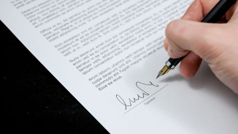 student signing a legal document
